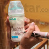 Tribune-Star/Joseph C. Garza<br /> Marked milk: Booker T. Washington High School student Danielle Harrison writes the name of her son, Hunter Norton, on a bottle before the start of class Tuesday at Booker T. Washington High School.
