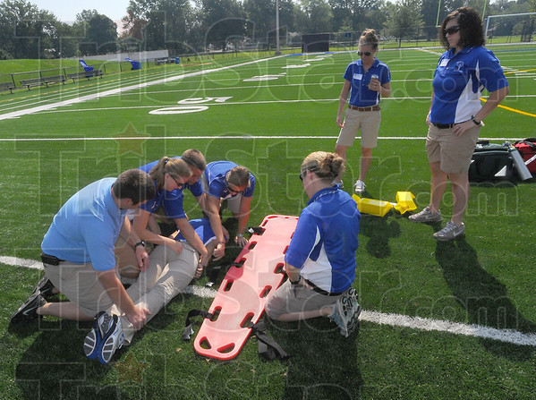Observe and do: Indiana State athletic trainers take turns practicing moving an injured person to a backboard during safety exercises Monday at Memorial Stadium.