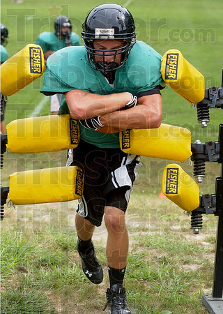 Breaking through: Cole Lydick runs through a drill Monday afternoon at Viking football practice.