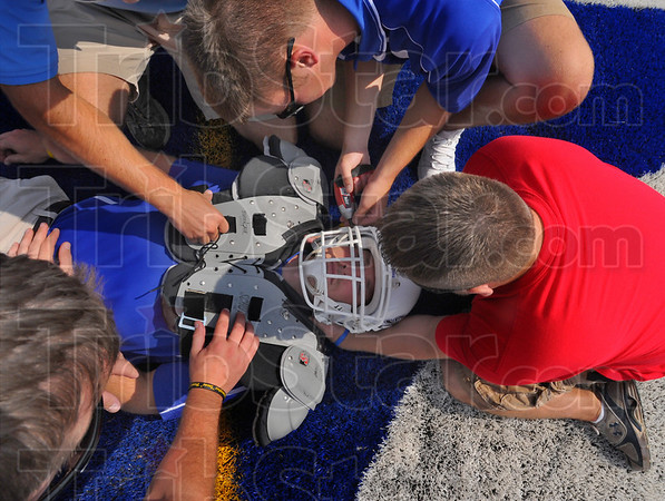 Stabilized: Indiana State University Athletic trainer Josh True plays the part of football player while David Hassler of Rose-Hulman stabilzes his head. Nick Arnold uses a battery powered screwdriver to remove the facemask of the helmet.  Dave Dziedzicki and Brad Yeargin assist. The practice was part of an emergency services collaboration drill held at ISUs Memorial Stadium Monday.