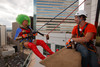 "(Denver, Colorado, Aug. 27, 2010)<br /> Caleb Vesely (right), an Over the Edge technical staff member, helps Nuclia Waste, in a Wonder Woman costume, rappel off the edge of the 28th floor.  ""Over the Edge,"" a benefit for the Cancer League of Colorado, at One Lincoln Park in Denver, Colorado, on Friday, Aug. 27, 2010.<br /> STEVE PETERSON"