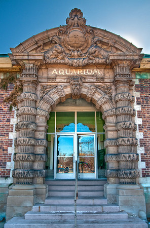"The entrance to Belle Isle Aquarium. Apparently Mayor Kilpatrick cut funding for this place and closed it down. It happened to be the oldest Aquarium in the country, the only one in Michigan, and one of the top 10 best places for fish (I guess they invented some great way of taking care of them or something). So sad that it was closed.  On this special saturday the ""Friends of Belle Isle Aquarium"" opened up the aquarium to try to raise awareness and get it re-opened. There was a great turnout and it was hard to take pictures without people in them!  In this shot I had to wait quite a while for there to be no people in it. You can also see in the upper right corner that the sun was pretty bright and I had to get close to the building so that the sun would be hidden behind it!"
