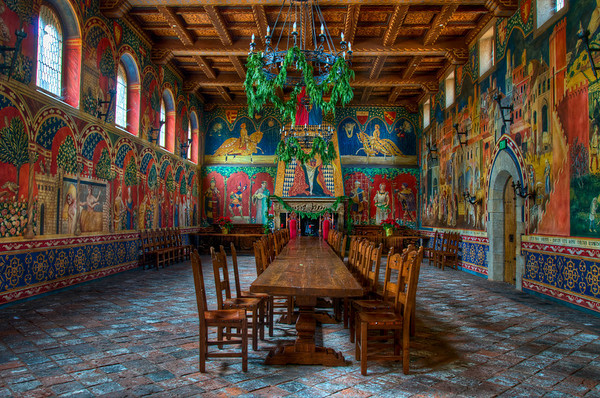 The great hall at Castello di Amorosa is a very eleborate room. The great hall features frescoes painted by two Italian artists who took about a year and a half to complete and showcases a 500 year old fireplace.  I had to wait several minutes for people to clear out before I could capture this photo. The folks behind me were kind enough to wait for me to get my 5 shots before coming in to explore themselves.  The castle interiors, which include 107 rooms on 8 levels above and below ground, cover approximately 121,000square feet (11,200 m2). Among many other features it has: a moat; a drawbridge; defensive towers; an interior courtyard; a torture chamber; a chapel/church; a knights' chamber; and a 72 by 30feet (9.1 m) great hall with a 22-foot (6.7 m)-high coffered ceiling.  The masonry, ironwork and woodwork was fashioned by hand using old world crafting techniques. Building materials included 8,000 tons of locally quarried stone, in addition to paving stones, terra cotta roofing tiles and some 850,000 bricks imported from Europe. Extending into the hillside adjacent to the castle lies a labyrinth of caves some 900feet (270 m) in length. Beneath the castle are a 2-acre (8,100 m2) barrel cellar and tasting rooms where visitors can sample the wines-all sold only at the Castle.