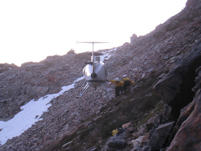 Emergency personnel prepare to load John into the helicopter.  The chopper is small, so one of them was required to stay the night at this bivy site.