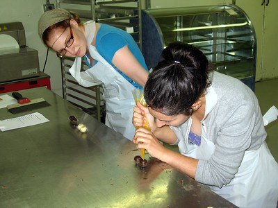 Alyssa pipes fresh mango and passionfruit filling into chocolate shells, while Laura looks on