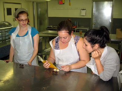 Katie pipes fresh mango and passionfruit filling into chocolate shells, while Laura (l) and Alyssa look on