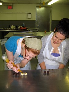Laura pipes fresh mango and passionfruit filling into chocolate shells, while Alyssa looks on