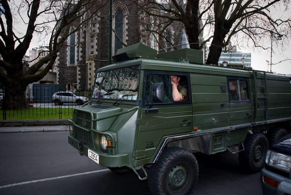 Army vehicle passing Christchurch Cathedral in Christchurch Square.