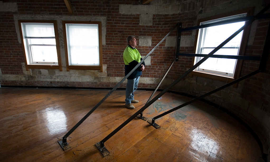 Local builder checking reinforcing beams now holding cracked walls in heritage building