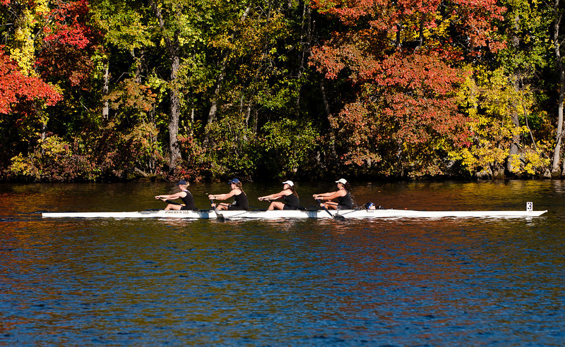 Girls varsity four racing by the fall foliage