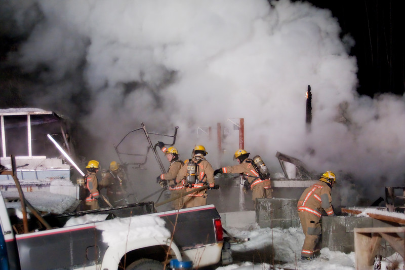 Firefighters pull burning debris from the fire to uncover the heat beneath.