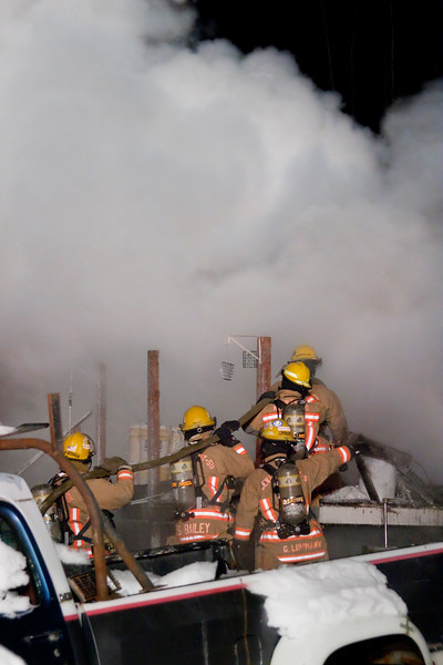 Firefighters work their hoseline to knock down heat.