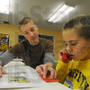 Hands on help: Rose-Hulman freshman Ethan Hixon helps Brian Langer, a third grader at Fuqua Elementary School, with his reading skills. Langer uses a Toobaloo, a simple device to help him hear his own voice as he reads aloud.