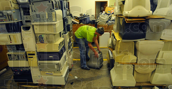 Room for more: Goodwill employee Brian Moseman stacks e-scrap in to be recycled in the work area of the building Thursday afternoon.