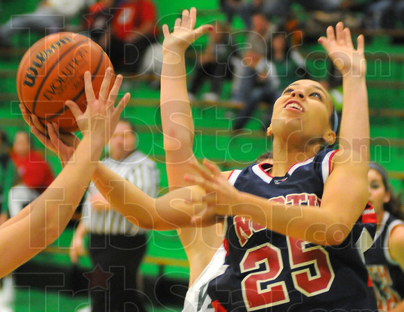Heavy traffic: Patriot forward Jenny Barnhill finds herself in a crowd near the basket. A defender shoves the ball in addition to applying pressure from in front.