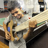 Guitar man: Chauncey-Rose student Savaughn Johnson picks his guitar made of recycled materials during judging of the Goodwill Art Contest Thursday morning.