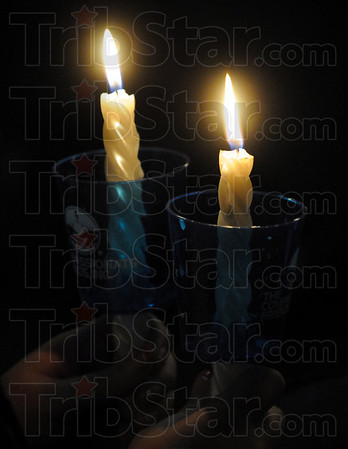 Detail: A participant holds two candles during Sunday's event .