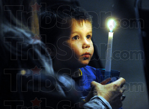 Candle: Two-year-old Brody Feider helps hold a candle in honor of Lanie Roby Sunday evening.