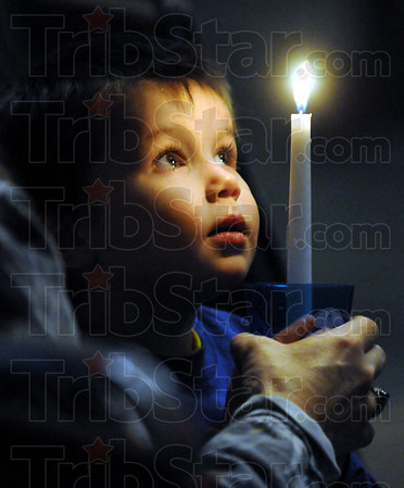 Candle kid: Two-year-old Brody Feider holds a candle for Lanie Roby during a ceremony Sunday night.