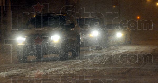 Blizzard: Cars creep along Wabash Avenue Sunday night as blowing and drifting snow cover the downtown area.