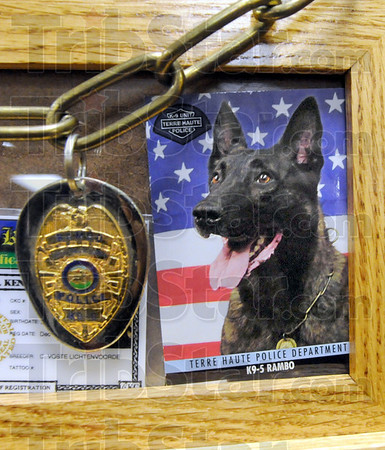 K-9 Rambo: the wooden box holding the ashes of Terre Haute Police Department K-9 Rambo sits on the podium with his identification card and shield.