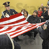 Flag for Rambo: Terre Haute Police Department Honor Guard members fold a flag honoring recently passed K-9 Rambo during a ceremony at police headquarters Friday afternoon. Rambo's handler, former officer Dan Parker watches from his seat.