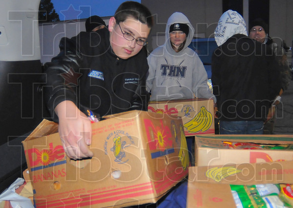 Helping out: Tanner Shipman, left, and other members of the Terre Haute North High School Junior ROTC helped load some 440 Tribune-Star Christmas baskets early Friday morning.