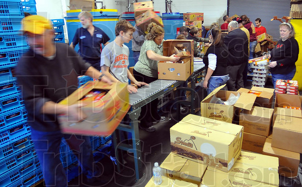 Many hands: About twenty volunteers, Tribune-Star employees, family and friends, work assembling Christmas food baskets Thursday morning at the paper's production facility.