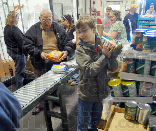 Pitching in: T.J. Rutan, center and about twenty other volunteers assemble Christmas foood baskets at the Tribune-Star production facility.