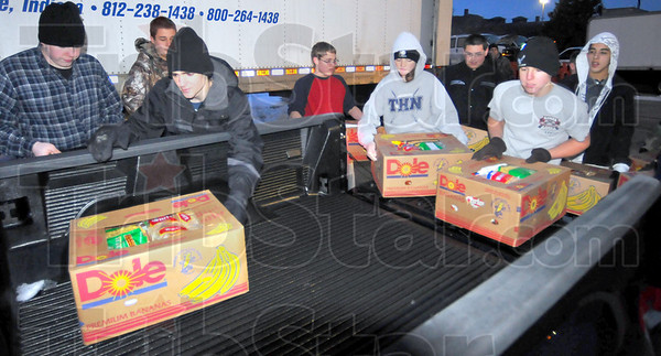 Giving back: Members of the Terre Haute North High School Junior ROTC help load food baskets onto a volunteer's truck early Friday morning.