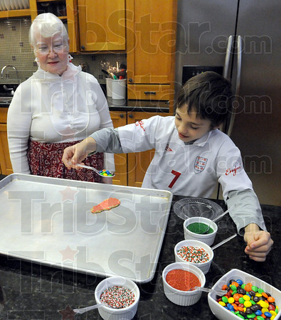 Mrs. Claus: Nine-year-old Moses Hamm adds some candy to a cookie he's preparing to eat at the Clabber Girl kitchen Friday evening under the watchful eye of Mrs. Claus.
