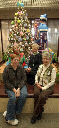 "Winners: ""Santas' Mail Room"" was the theme of the winning Christmas display built by members of the Vigo County Home Extension Chorus at the main office of First Financial Bank. Members Norma Laxer and Sandy Shanks, front, and Julia Reed and DeDe Schindel pose with part of their creation. Each year bank branch offices are decorated by various Wabash valley organizations, each hoping for a share of the thousands of dollars in prize money."