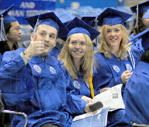 We did it: Graduates from ISU in Business and Marketing Kyle Colson, Whitney O'Brien and Sarah Barnett look to their parents in the audience at graduation Saturday afternoon.