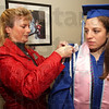 Preparations: Dawn Wimsett of the Indiana State Unversity Office of Registration and Records, helps graduate Makenzie Hopf with her cap and gown.
