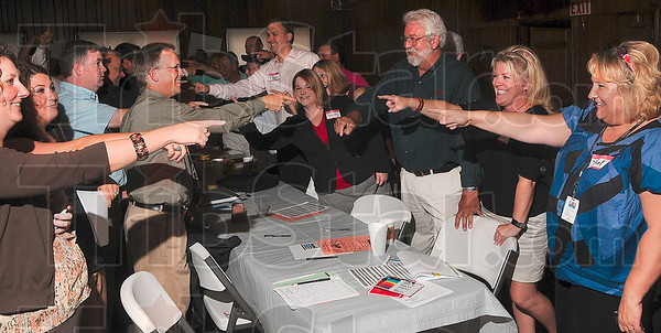 Tribune-Star/Joseph C. Garza<br /> Staying connected: Participants in Tuesday's Chamber of Commerce membership drive point to one another during a team building exercise at Clabber Girl.