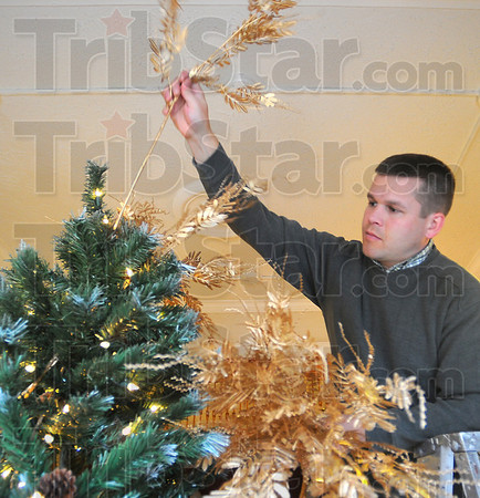 Deck the halls: Tommy Kleckner of Indiana Landmarks places the pieces of teh tree topper on the Christmas tree in the front window of the Kelly House.