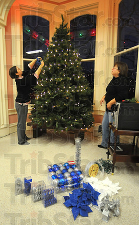 Deck the halls: Alyssa Murphy ties blue poinsettias onto a Christmas tree while her mother, Pam Kapple watches. The two were decotrating the tree in Honey Creek Title Thursday evening getting it ready for the Farrington Grove Home tour today.