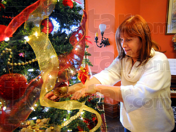 Merry and bright: Kaylynn Sanders adjusts the Christmas tree in her Farrington Grove home. She is heading up the Farrington Grove Christmas Open House again this year.