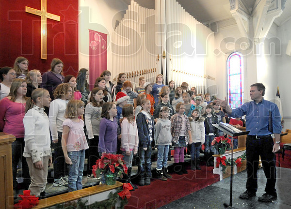 Instruction: Dan Taylor arranges members of the Terre Haute Children's Choir for their rehearsal at the Central Presbyterian Church Wednesday afternoon.
