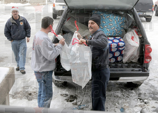 Donations: Terre Haute firefighters unload presents at St. Ann's Monday morning.