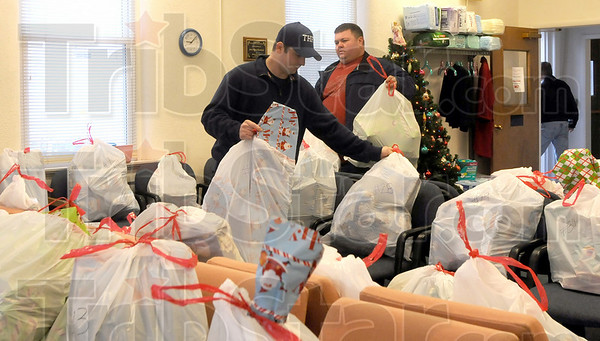 Bundles: Terre Haute firefighters deliver bags of presents to the St. Ann's clinic Monday morning.