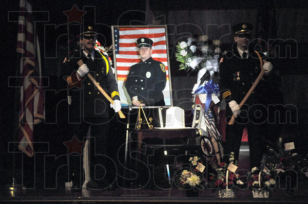 Honor guard: Two firefighters stand on each side of a portrait of Chad Null during Monday's memorial service at Sullivan High School.