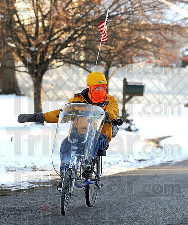 B-r-r-r-r-raving the cold: In spite of temperatures in the teens, Richard Brooks checks for cross traffic as he prepares to make a turn onto Crawford Street from south 29th Street Tuesday evening. He's riding his bike home from his job at Lenex Steel located at 6th and Vorhees.