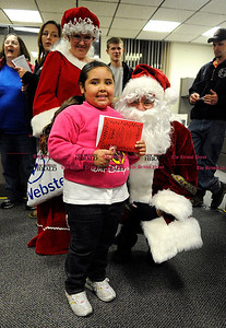 12/1/2010 Mike Orazzi | Staff Kadyn Matos,5, meets Santa during the 59th Annual Carol Sing and the 20th Annual Holiday Lighting Ceremony held at Webster Bank on Main Street in Bristol on Wednesday night.