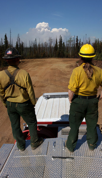 Danny Clemons and Jess Young watch the smoke column from the far flank of the fire as activity picks up in the midday heat.