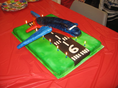 The finished product.  The base is made from brownie and the plane is molded from Rice Krispies Treats.  Everything else is made from rolled fondant and food coloring, except the candles, letters, skewers, and metal support.