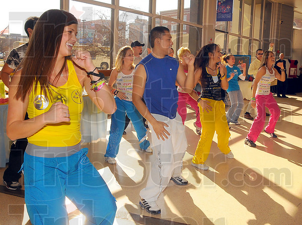 Zumba: Lauren Krieble(yelow top) and Misael Refugio, along with others give a demonstration of Zumba at the Community Health Fair Sunday afternoon at Hulman Center. They are from Ultimate Health and Fitness.