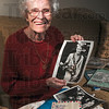 Tribune-Star/Joseph C. Garza<br /> Part of Indiana aviation history: Drina Welch Abel displays a photo of Amelia Earhart in her apartment Sunday at Anthony Square. The photo of Earhart  was taken at the dedication of the Welch family's airport in Anderson in 1929.