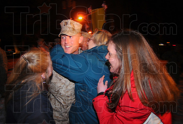 Back home: Corporal Eric Frahm gets a hug from his mother Earlene while his sister Eunice, right and girlfriend Melissa Rhodes wait their turn.