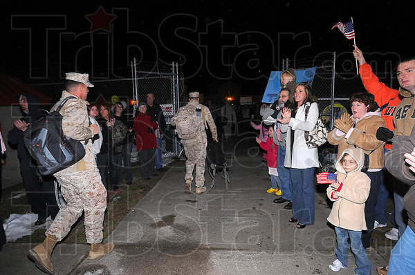 Worth the wait: The returning Marines of Kilo Company are cheered as they walk through the gate of the reserve center late Friday night.